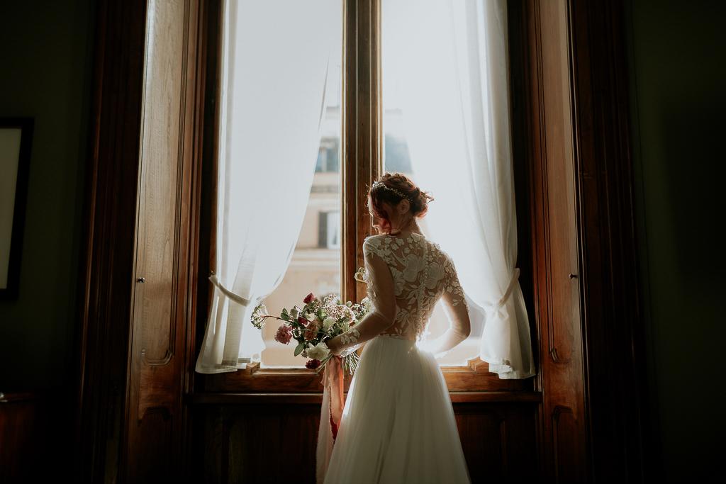 la sposa col vestito bianco davanti alla finestra