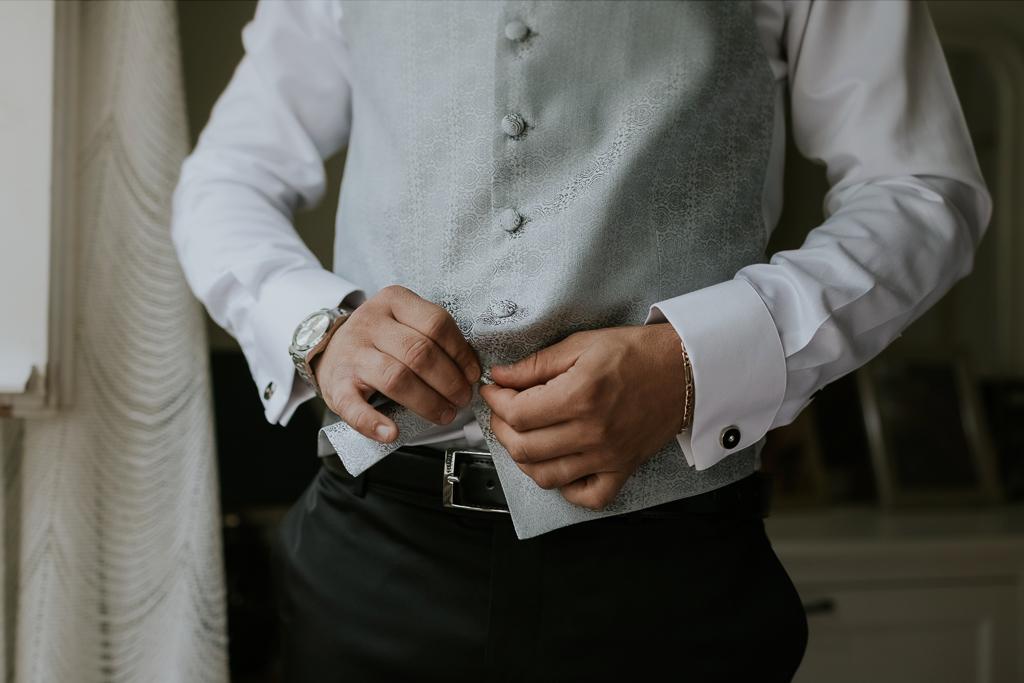 sposo abbottona il gilet per il matrimonio a roma