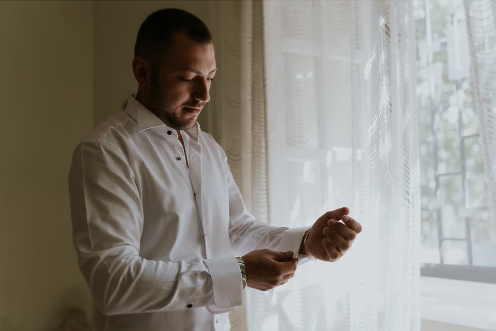 lo sposo si abbottona la camicia per il suo matrimonio a roma