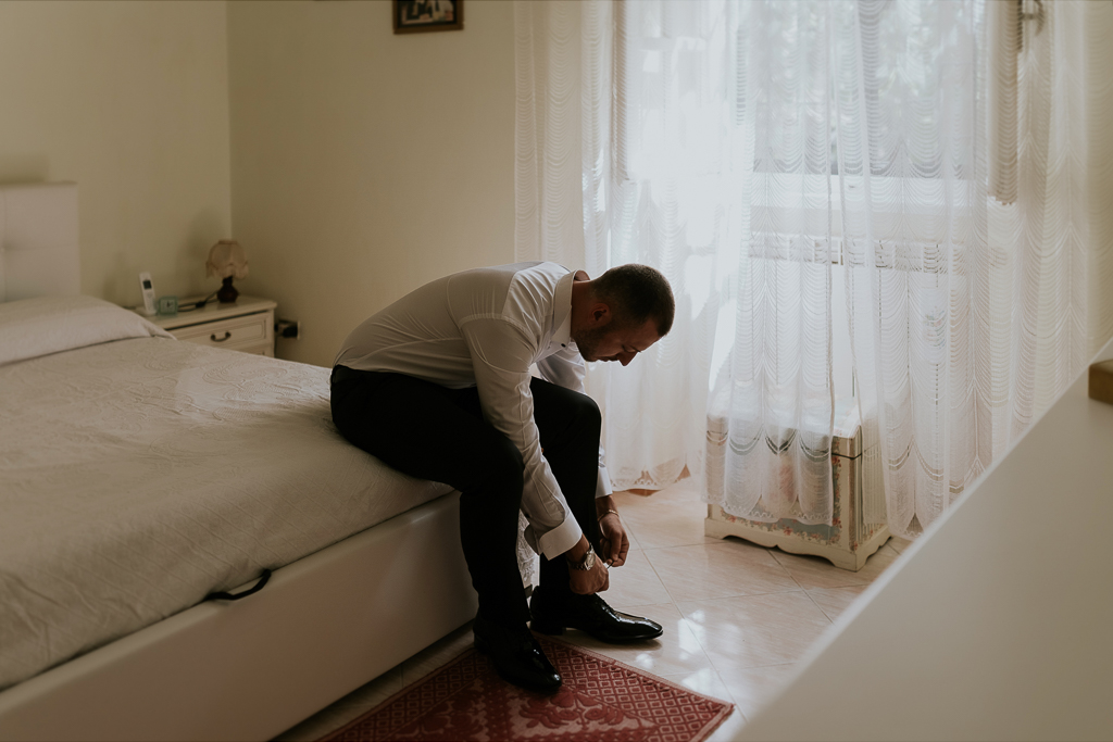 lo sposo allaccia le scarpe per il matrimonio a roma