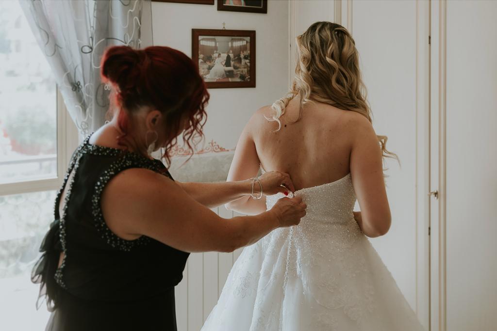 mamma aiuta la sposa per chiudere il vestito