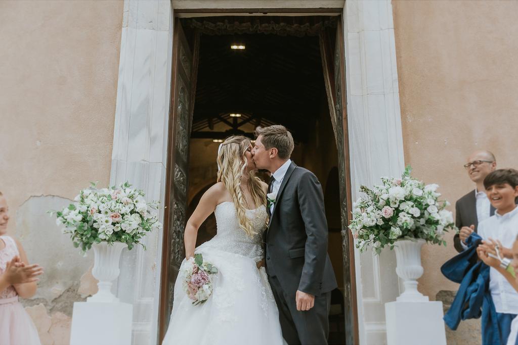 sposi si baciano dopo il lancio del riso